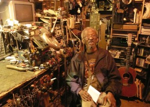 Blues guitarist Harvey Knox sitting in his home workshop.